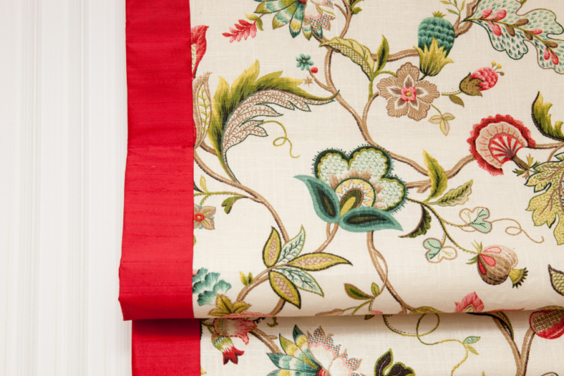 a window blind in a floral pattern with a red border