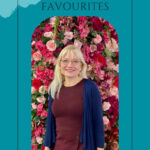 Spring Beauty Must Haves - April J Harris photographed against a wall of flowers
