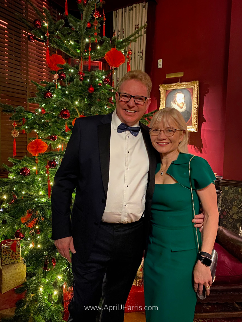 The Holiday Season at the Hearth and Soul Link Party -April and Guy Harris standing by a Christmas tree at Palace House