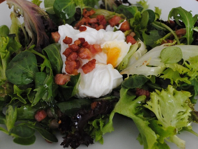 Salade Frisée aux Lardons served on a plate