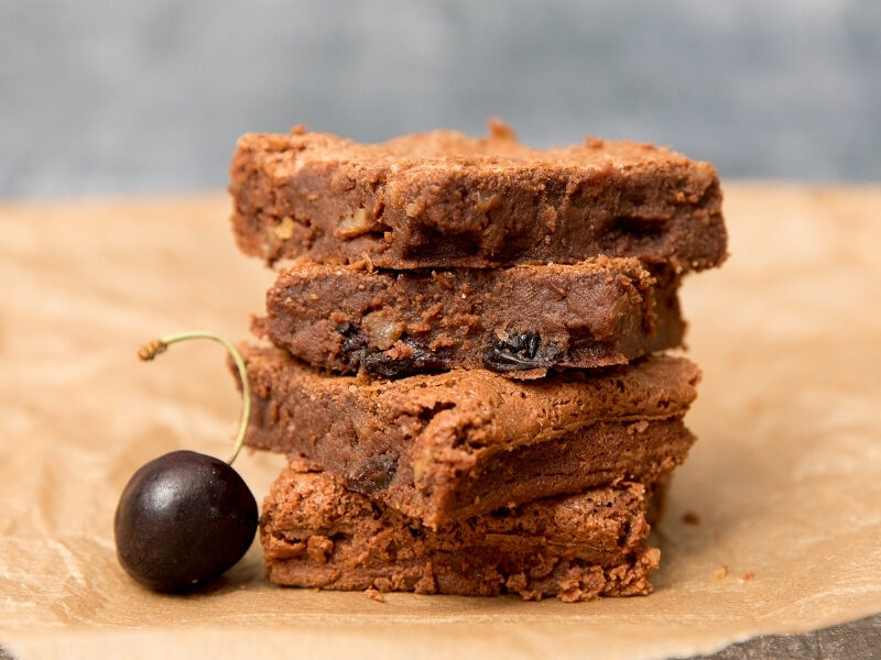 A stack of red wine brownies with a cherry alongside